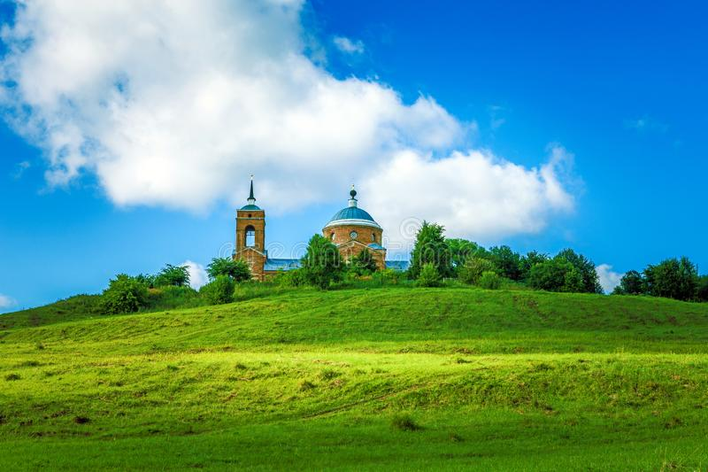 Traditional Russian landscape - summer with green hills with grass on the background of the old Russian Church.  stock photo