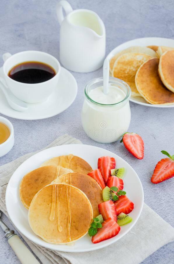 Traditional Russian pancakes on kefir with honey, sour cream, fresh strawberries and kiwi on a white plate with a cup of coffee. stock image