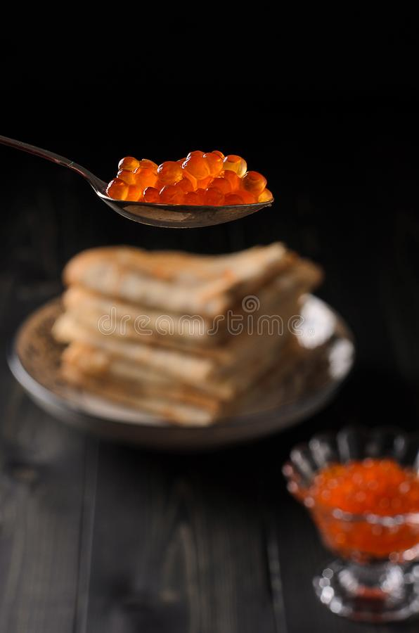 Traditional Russian pancakes with red caviar. On a rustic wooden table stock photos