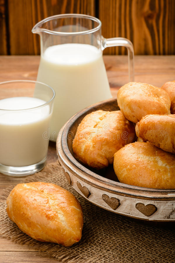 Traditional russian pastry piroshki and milk on wooden table. royalty free stock photos