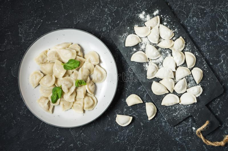 Traditional russian pelmeni, ravioli, dumplings with meat on black concrete background. Top view stock photos