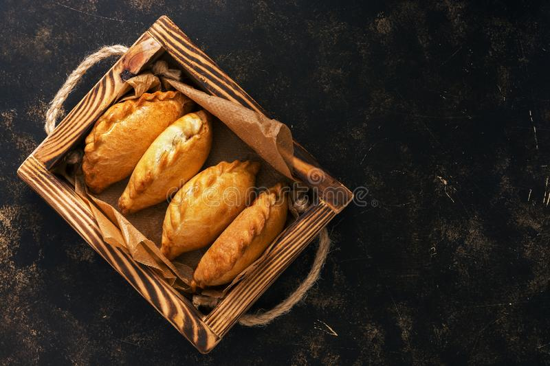 Traditional Russian pies in a wooden tray on a dark rustic background. Russian pirozhki ,baked patties. Top view, copy space, flat. Lay royalty free stock photos