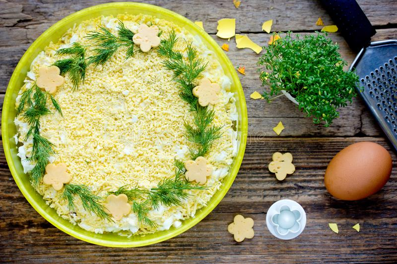 Traditional russian salad mimosa decorated with cheese flowers royalty free stock photos