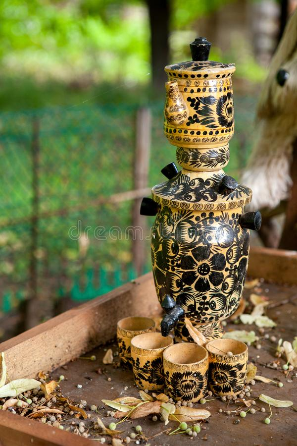 Traditional russian samovar with few cups for tea. Imitation of traditional russian teapot - samovar with few cups for tea, all made of wood with drawing, on a stock images