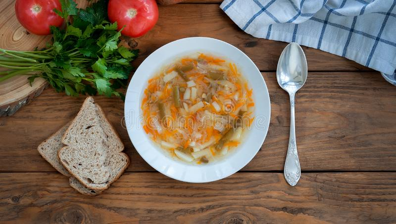 Traditional russian soup shchi with sour cabbage in a white plate with spoon and bread on a wooden background. Top view stock image