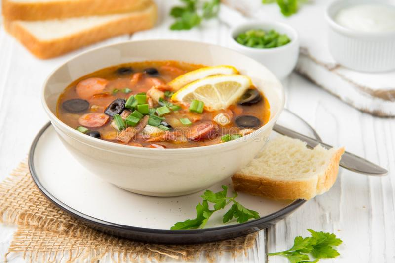Traditional Russian soup Solyanka with beef, chicken, sausage, lemon, olives and pickled cucumber. Delicious hot lunch, homemade royalty free stock images