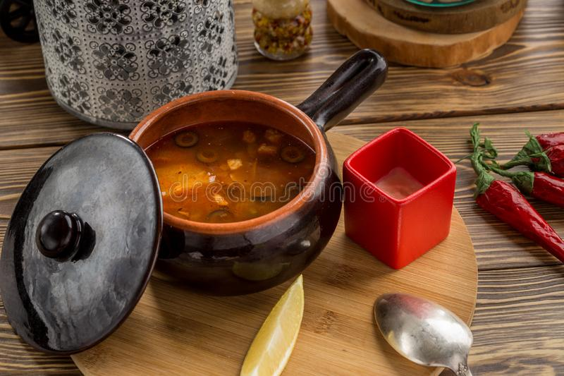Traditional Russian soup solyanka with smoked meat and olives in clay pot on wooden table stock images