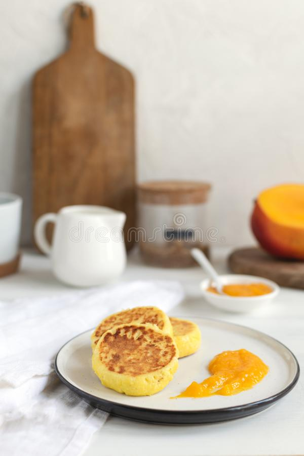 Traditional russian syrniki or cottage cheese pancakes served with mango, coffee, milk pitcher, healthy breakfast stock photography