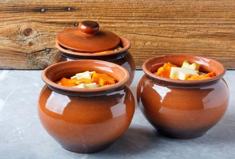 Traditional rustic home vegetable ragout in three clay pots on beautiful table top. stock image
