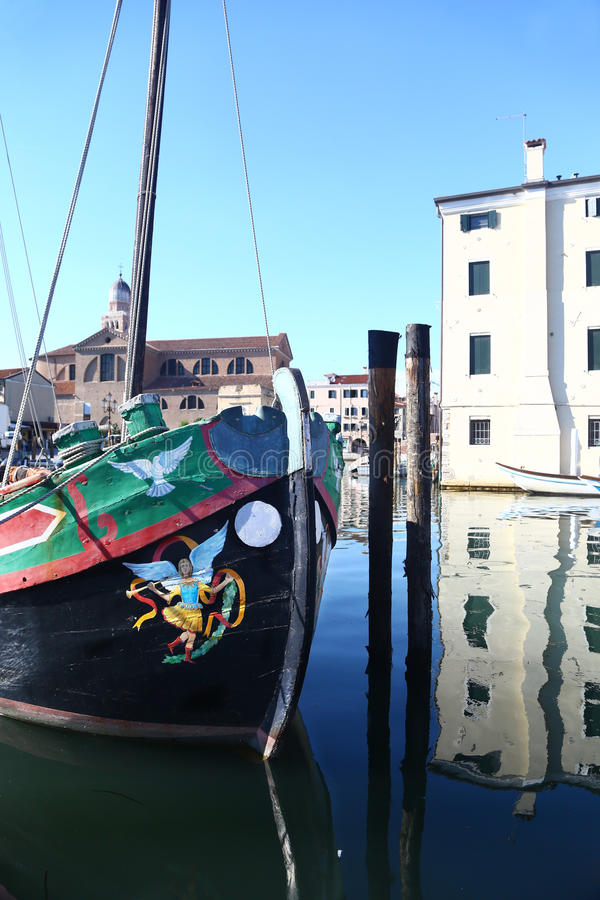 Traditional sailboat & canal in Chioggia, Italy. Traditionally painted sailboat in canal of Chioggia, Italy stock photos