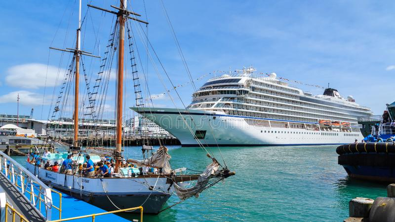 A traditional sailing ship and a modern cruise liner in port stock image