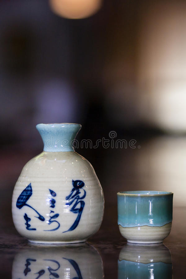 Traditional sake cup and jug. Traditional sake jug and cup on bokeh background royalty free stock photo