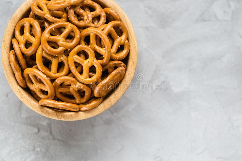 Traditional salty mini pretzels in wooden bowl on a gray backround royalty free stock image