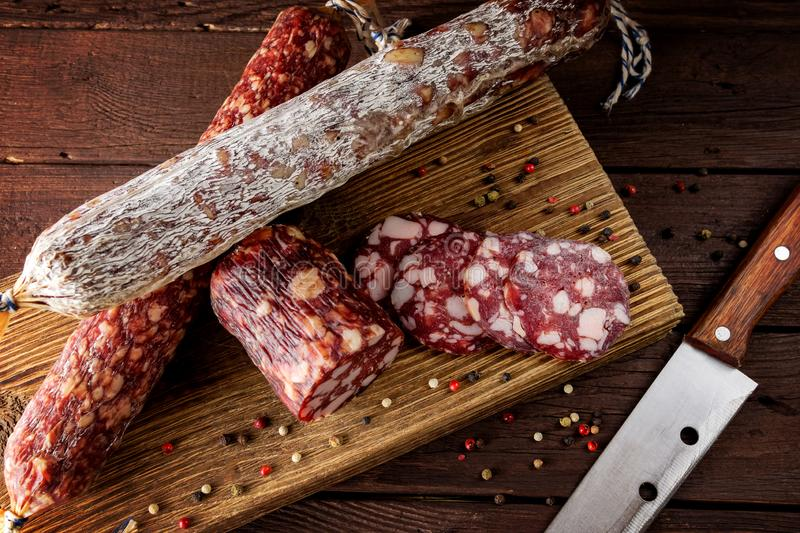 Traditional sausage and sausage with mold. Sliced sausage salami and  knife on wooden board with spices.top view stock images
