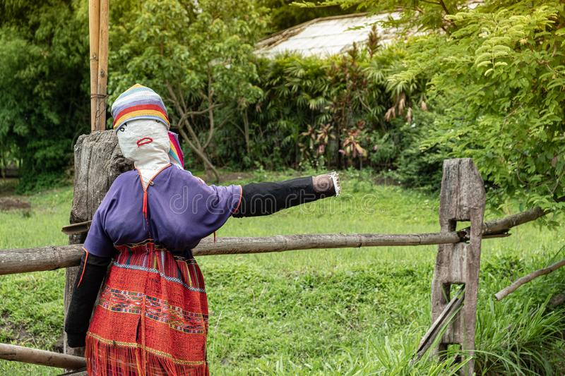 Traditional scarecrow dressed as hill tribe woman. In the north of thailand, she was in welcome posture in the front of local village to invite tourist go stock photos