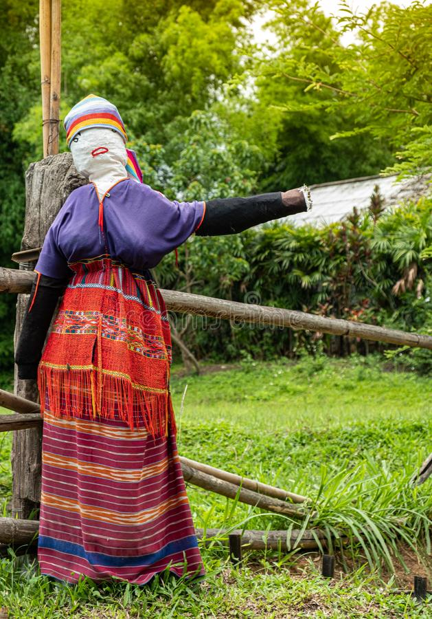 Traditional scarecrow dressed as hill tribe woman. In the north of thailand, she was in welcome posture in the front of local village to invite tourist go royalty free stock photo