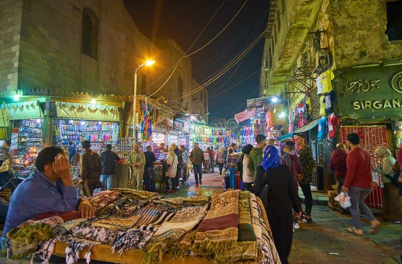 Traditional scarfs in Khan El Khalili Bazaar, Cairo, Egypt. CAIRO, EGYPT - DECEMBER 22, 2017: The crowded evening street of Khan EL Khalili market with multiple royalty free stock image