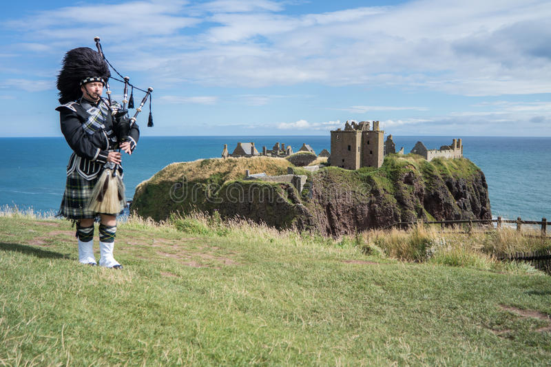 Traditional scottish bagpiper in full dress code at Dunnottar Castle royalty free stock photography