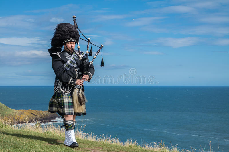 Traditional scottish bagpiper in full dress code at the ocean royalty free stock images