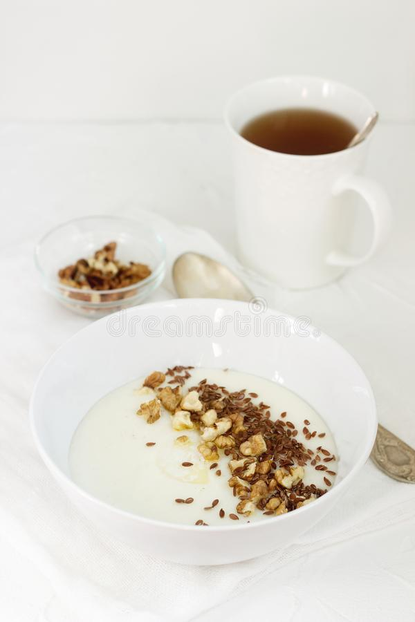 Traditional semolina porridge with butter, nuts and flax seed. A useful breakfast of porridge and tea. Rustic style. stock photos