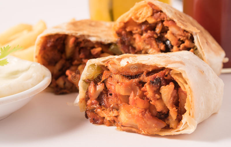 Traditional shawarma wrap with chicken and vegetables ,French fries ,cocktail and garlic paste in a white plate. stock photos