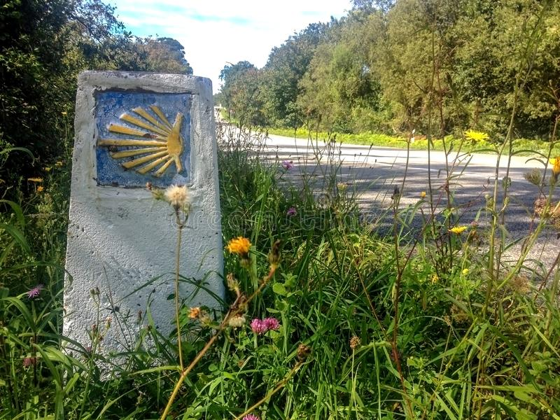 Traditional shell sign and arrow painted on the way. Direction sign for pilgrims in Saint James way, Camino de Santiago de stock photos