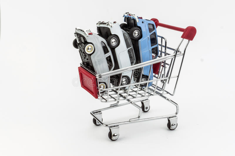 Traditional shopping cart full of miniature cars. Business concept stock photo