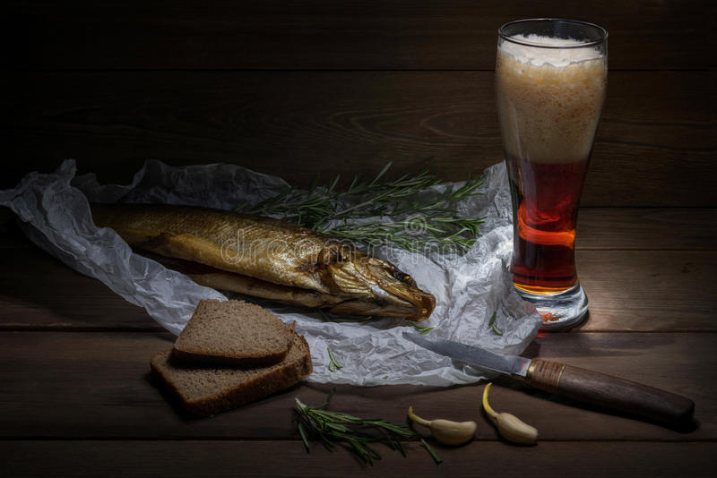 Traditional Siberian smoked fish wrapped in the wrinkles paper lie on the wood table near the damask knife and the bread stock photography