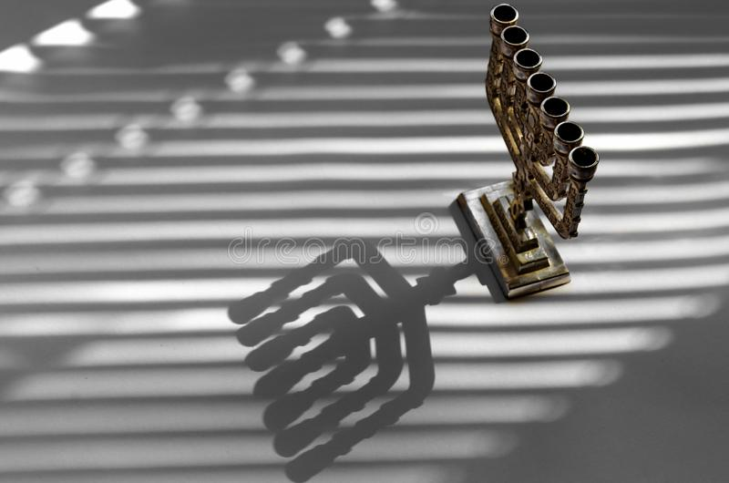 Traditional silver jewish menorah on a white background with stripes of shadow from the blinds royalty free stock photography