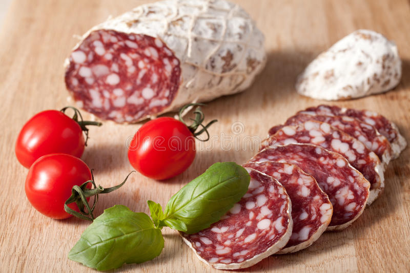 Traditional sliced salami on wooden board royalty free stock photos