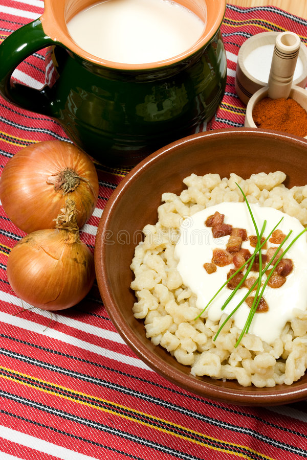 Traditional Slovak food. Dumpling (halusky) with sheep cheese (bryndza) with bacon, chives, onion and Zincica stock image