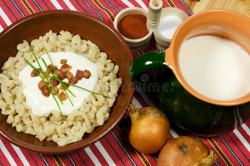 Traditional Slovak food. Dumpling (halusky) with sheep cheese (bryndza) with bacon, chives, onion and Zincica royalty free stock images