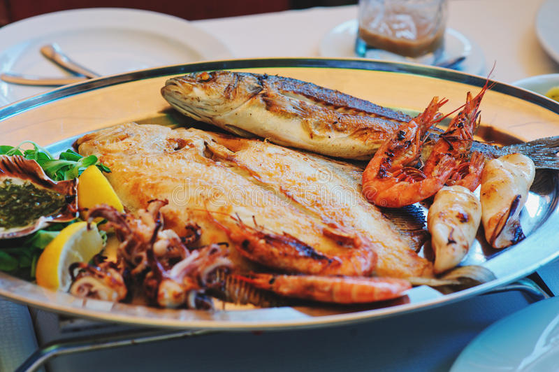 Traditional slovenian cuisine, mixed grilled fish and seafood with garlic oil. Selective focus stock images