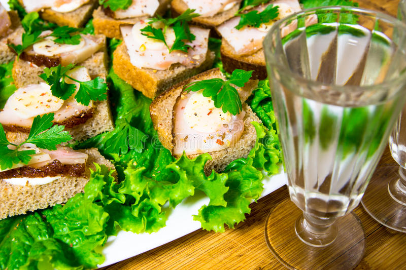 Traditional snack for Russian and Ukrainian people on the holidays. A sandwich with bacon, garlic and parsley under the glass of g. Enuine Russian vodka enuine royalty free stock images
