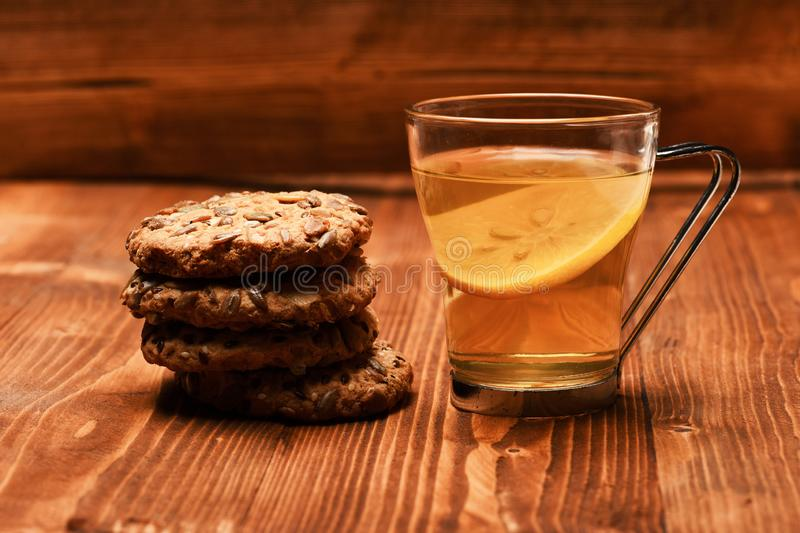 Traditional snack for tea time. Drink and homemade goods. Concept. Cookie made of oatmeal and tea cup with lemon on wooden background. Biscuits with seeds stock photo