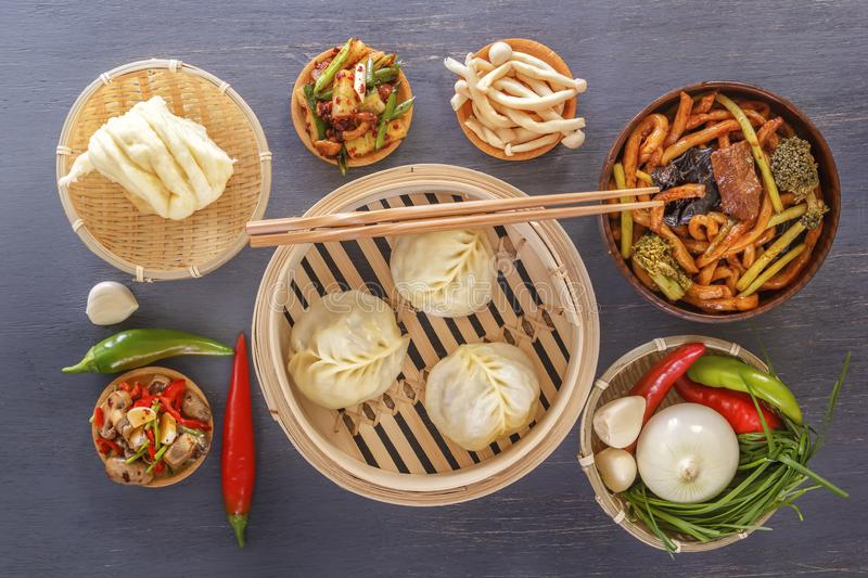 Traditional snacks of Chinese cuisine dim sum - dumplings, spicy salads, vegetables, noodles, steam bread. Top view stock photos