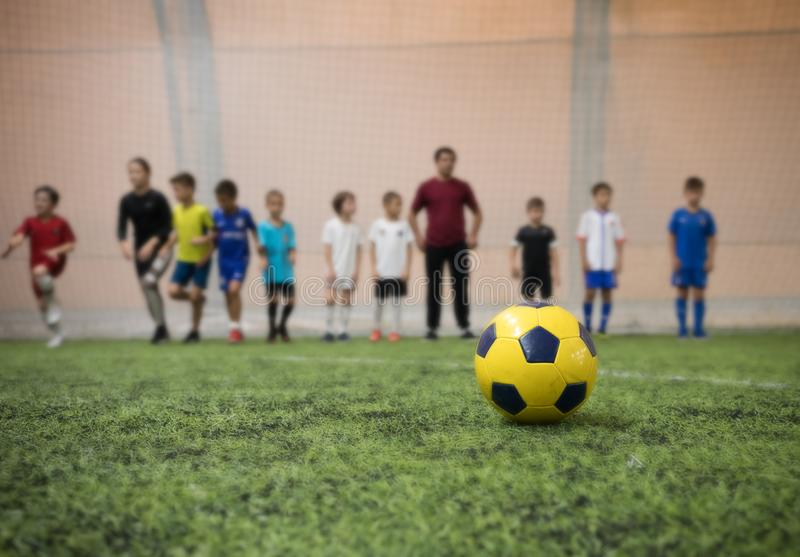 Traditional soccer ball on the football field on the background of children football players and their coach royalty free stock photography