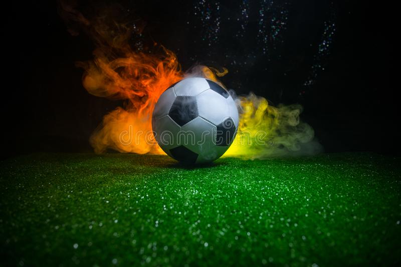 Traditional soccer ball on soccer field. Close up view of soccer ball (football) on green grass with dark toned foggy background. stock image