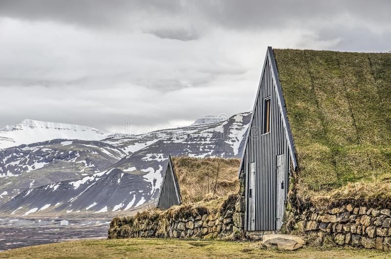 Traditional sod houses and mountains. Borgarnes, Iceland, February 28, 2019: two traditional grass-covered Icelandic huts on a hilltop, with snow-covered royalty free stock image