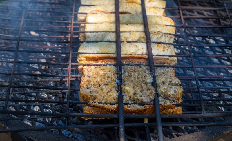 Traditional South African braai broodjies prepared on open coals. Traditional South African toasted sandwiches known as braai broodjies prepared on an open fire royalty free stock photos