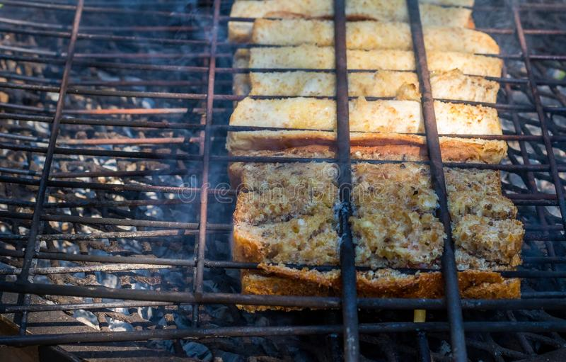 Traditional South African braai broodjies prepared on open coals. Traditional South African toasted sandwiches known as braai broodjies prepared on an open fire royalty free stock photography