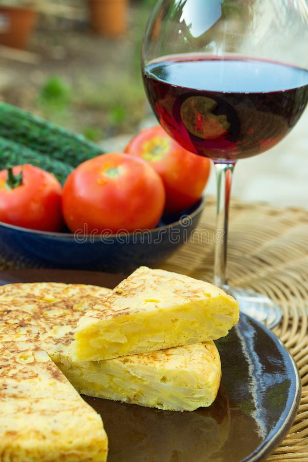 Traditional Spanish omelet tortilla frittata with potatoes eggs cut out wedge vegetables tomatoes cucumbers glass of red wine stock image