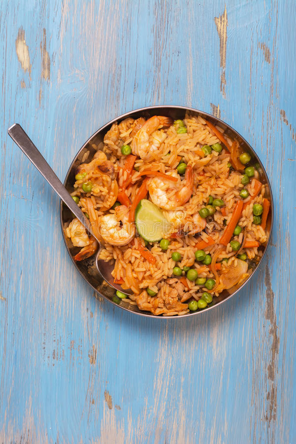 Traditional spanish paella dish with seafood, peas, rice and chicken stock images