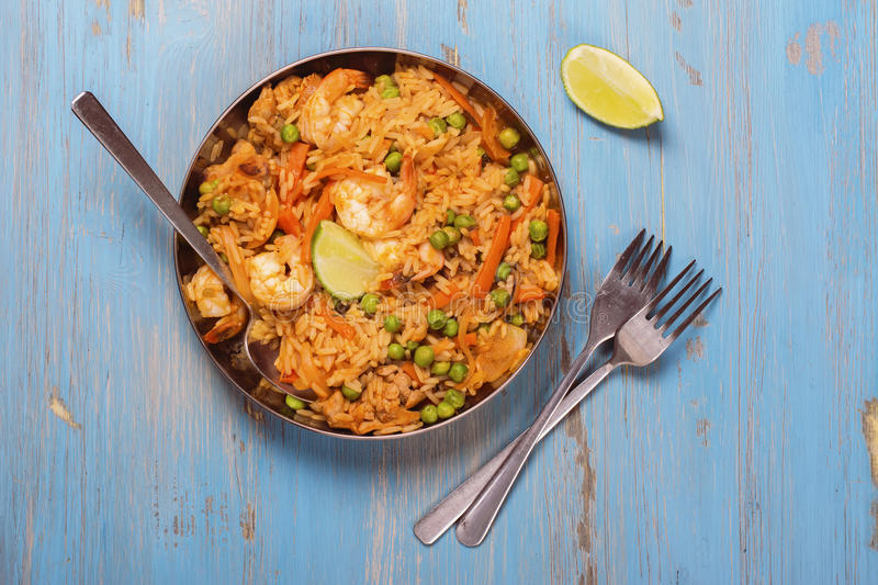 Traditional spanish paella dish with seafood, peas, rice and chicken stock photo