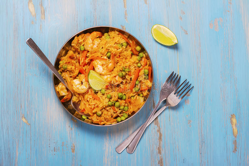 Traditional spanish paella dish with seafood, peas, rice and chicken stock image