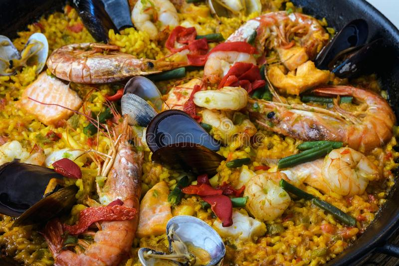 Traditional spanish seafood paella dish in a black pan. Mussels, Amandi and prawns on a pillow of rice. Close-up. stock photo