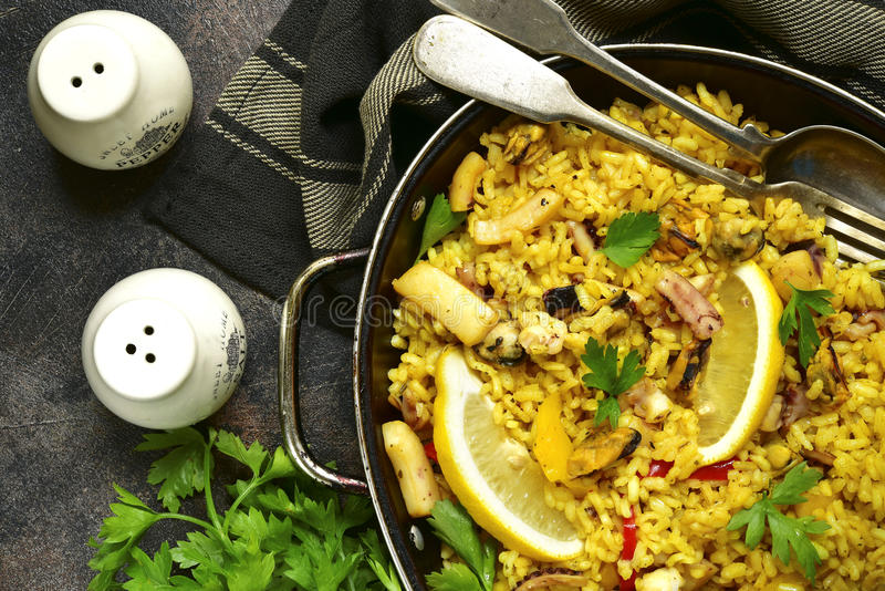 Traditional spanish valencian dish paella - stew with rice and. Seafood in a pan over dark rustic slate,stone or metal background.Top view royalty free stock image
