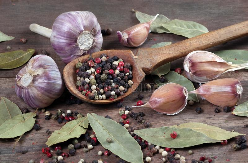 Traditional spices for the kitchen. bay leaf, mixture of various peppers in a spoon and garlic on a wooden table. Traditional spices for the kitchen. bay leaf royalty free stock image