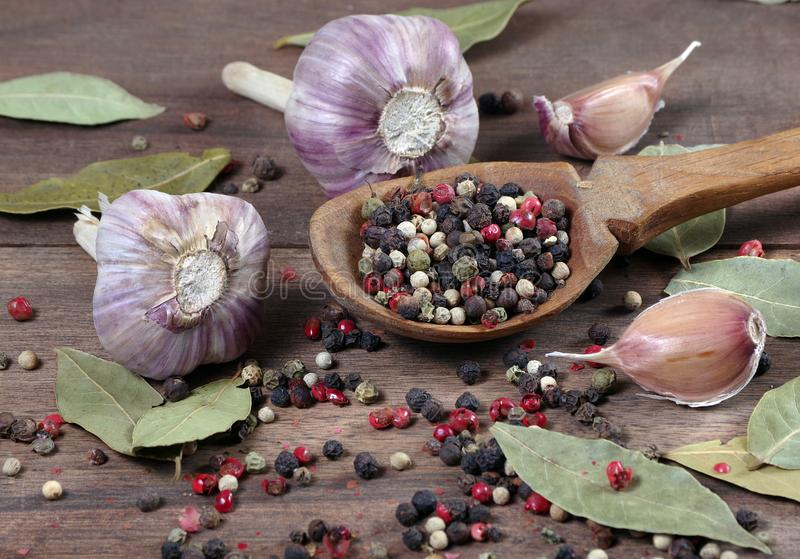 Traditional spices for the kitchen. bay leaf, mixture of various peppers in a spoon and garlic on a wooden table. Traditional spices for the kitchen. bay leaf stock image