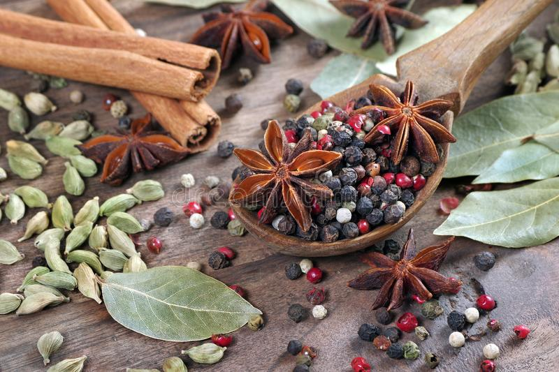 Traditional spices. mix of peppers in a wooden spoon, anise stars, cinnamon, cardamom and bay leaf on a wooden table stock photo